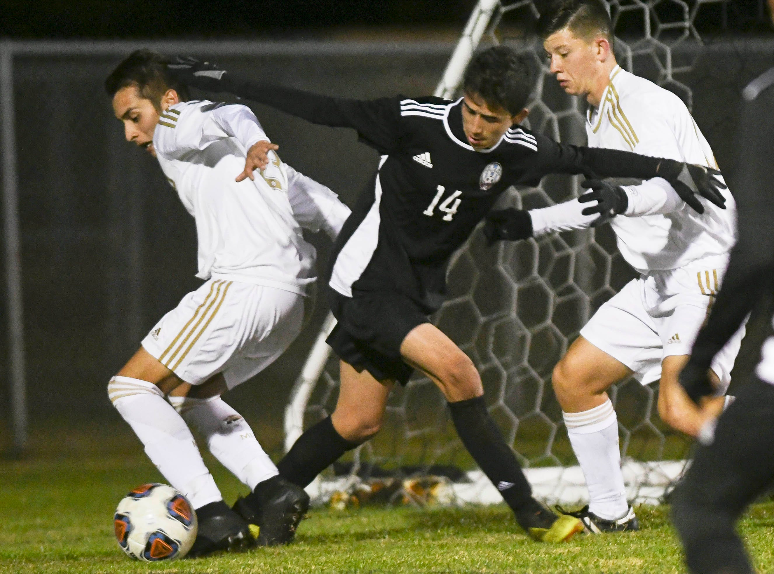 Luis Esteban Son of Rockledge is harassed by Ethan Mills (left) and Jake Sorensen of Merritt Island during Wednesday's District 12, Class 3A semifinal at McLarty Stadium