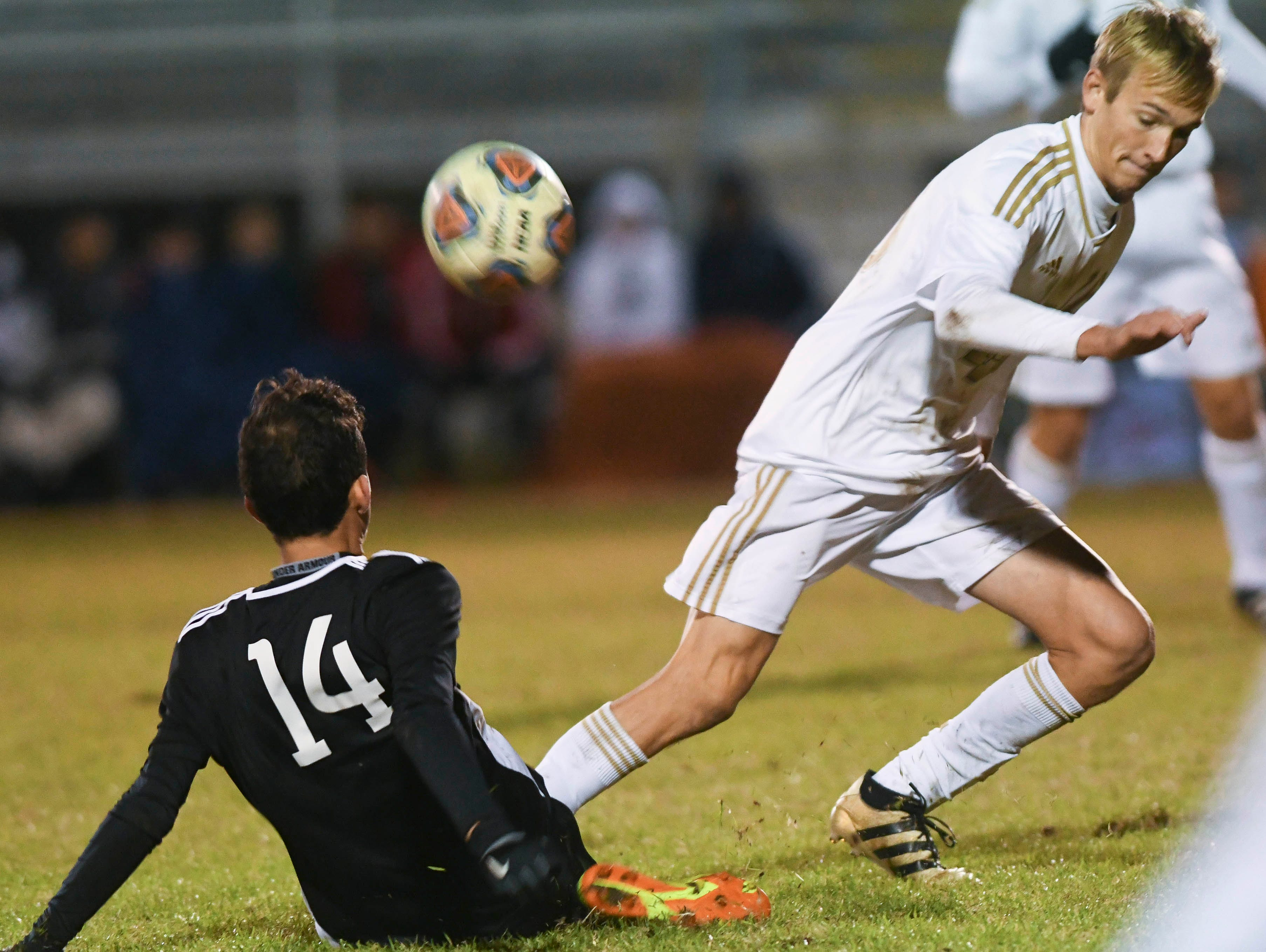 Luis Esteban Son tackles the ball away from Kaleb Bechtol of Merritt Island during Wednesday's District 12, Class 3A semifinal at McLarty Stadium