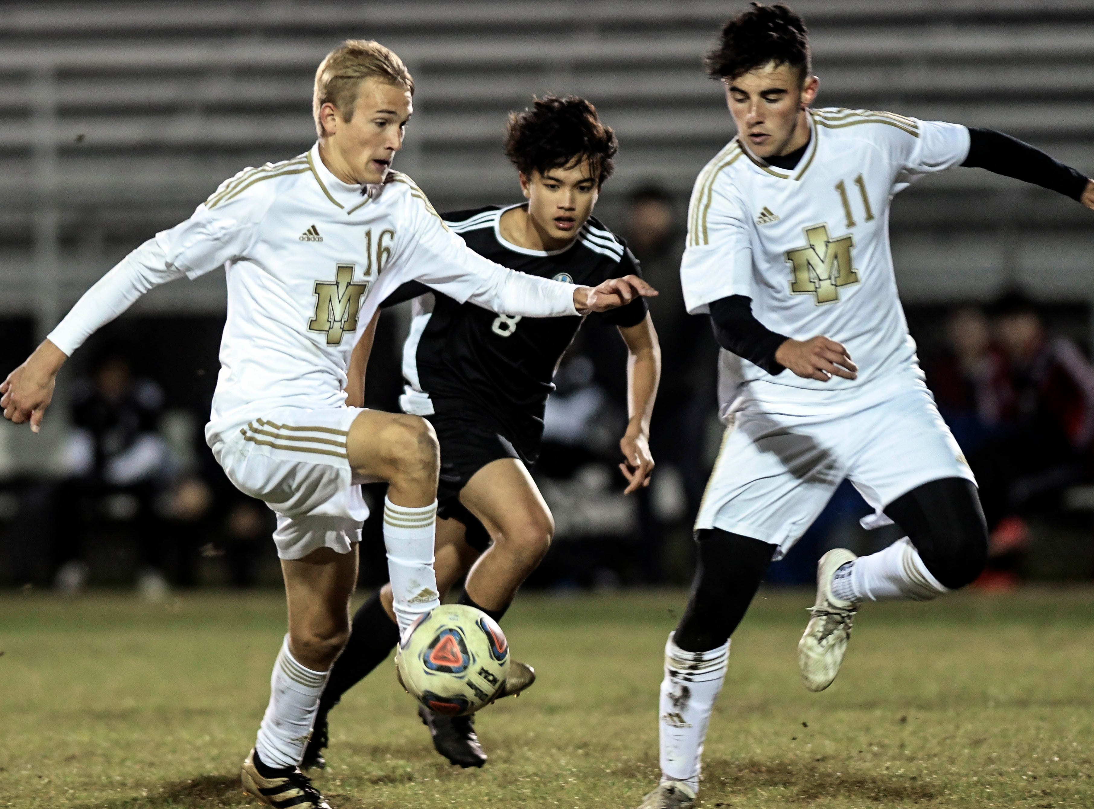 Kaleb Bechtol (16) and Andrew Sequeira (11) of Merritt Island keep the ball away from Andrew Inocencio of Rockledge during Wednesday's District 12, Class 3A semifinal at McLarty Stadium