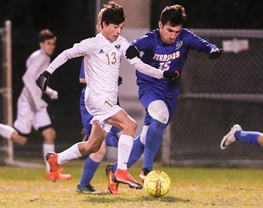 Eau Gallie's Jaxon Supernaw is closely guarded by Mickey Mikitarian of Titusville during a district tournament game.
