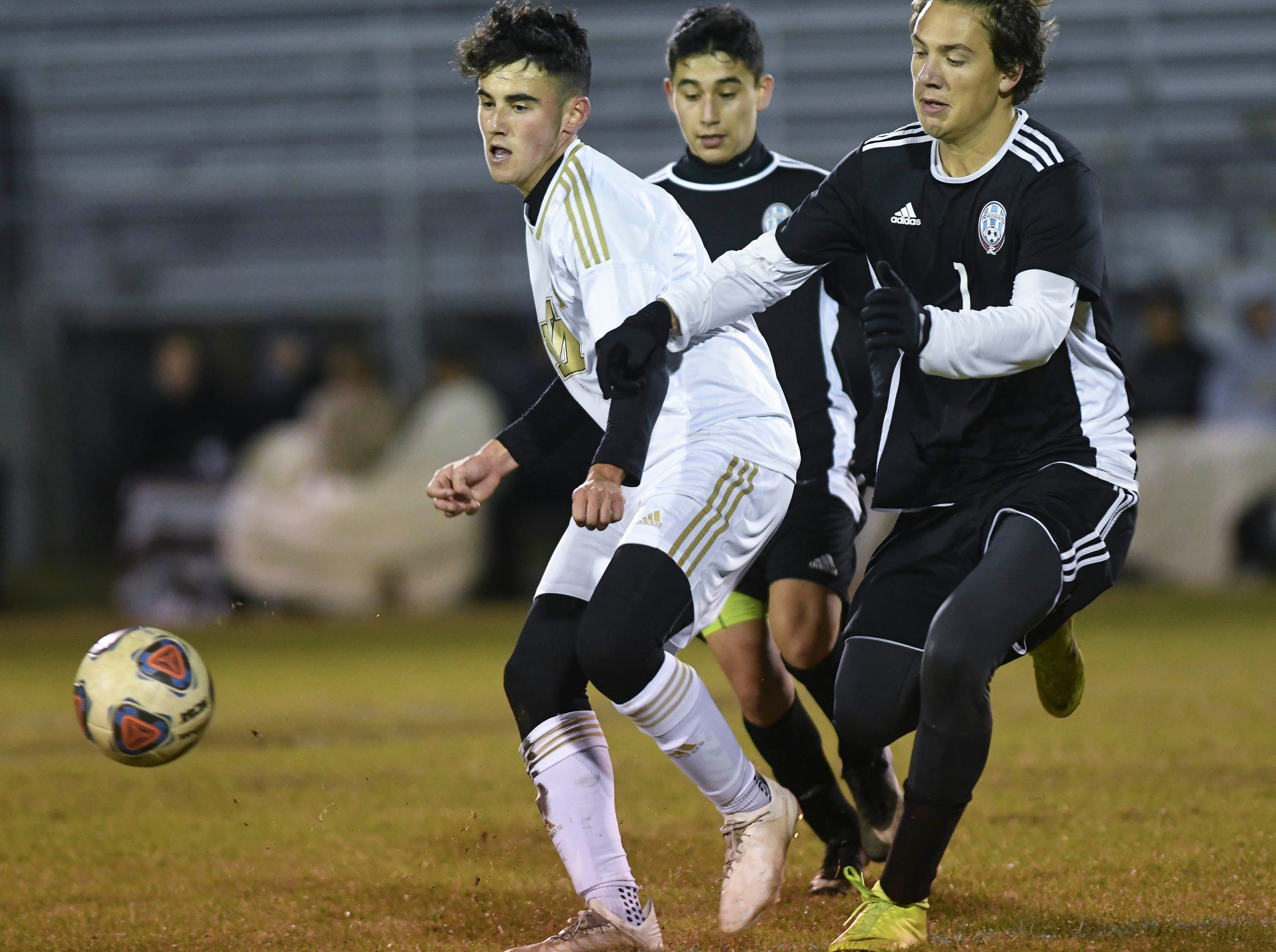 Arath Castaneda (5) and Richie Chamberlin of Rockledge pursue Andrew Sequeira of Merritt Island during Wednesday's District 12, Class 3A semifinal at McLarty Stadium.