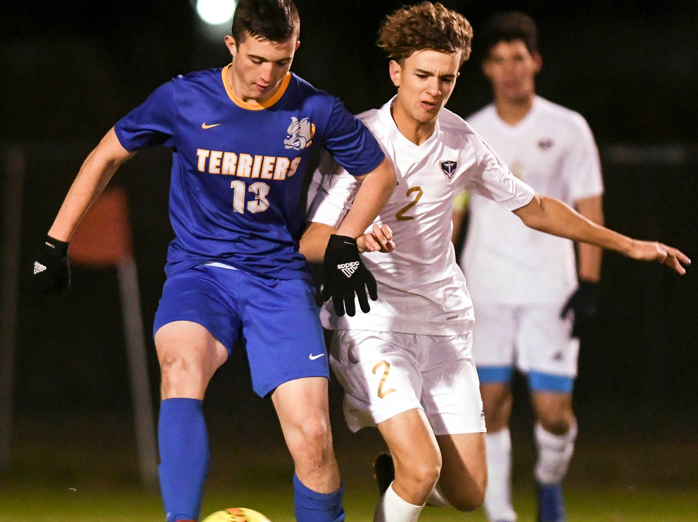 Titusville's Jeremy Pless (13) and Alex Masedo of Eau Gallie battle for possession of the ball during Wednesday's District 12, Class 3A semifinal at McLarty Stadium
