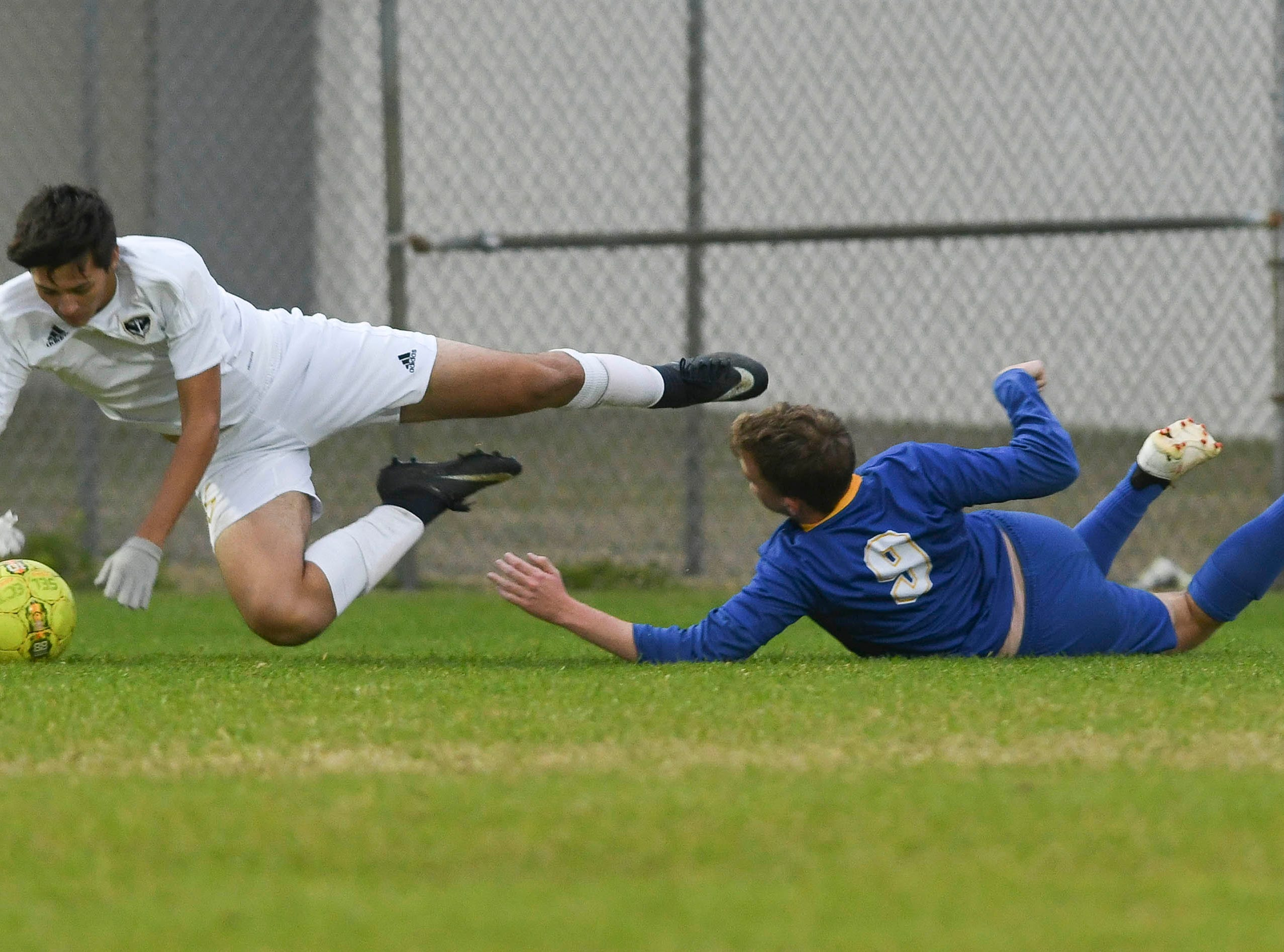 Sean Deavers of Eau Gallie trips over Titusville's David Colbert during Wednesday's District 12, Class 3A semifinal at McLarty Stadium