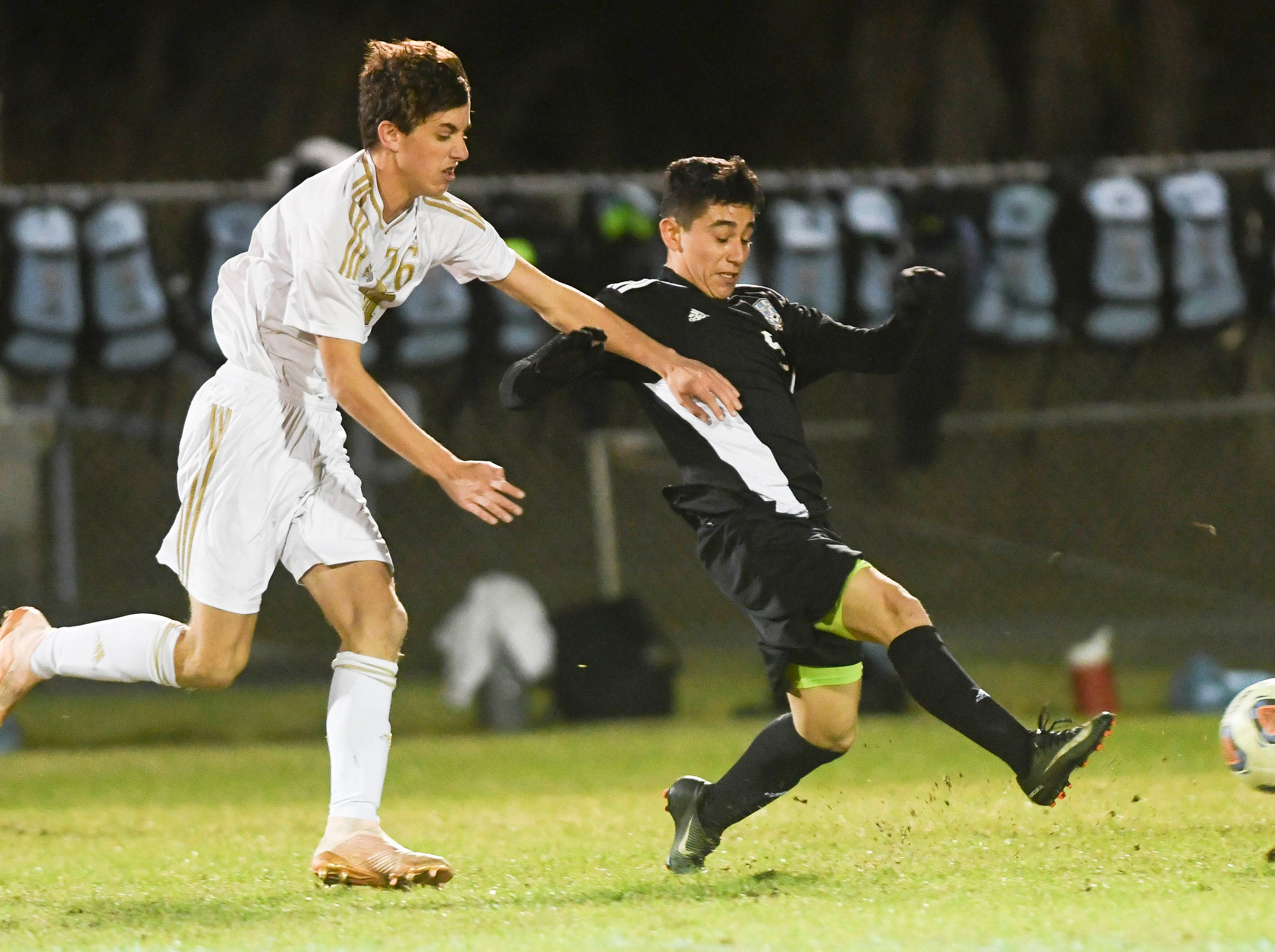 Arath Castaneda of Rockledge (5) directs the ball away from Seamus Feeney of Merritt Island during Wednesday's District 12, Class 3A semifinal at McLarty Stadium