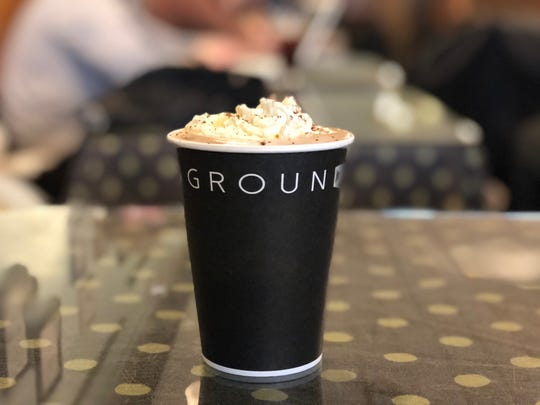 A hot chocolate sits on a table at Uncommon Grounds Coffee and Tea, with whipped cream and cocoa powder at the top. Jan. 25, 2019.