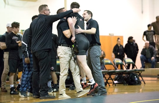 Kingsway's Ryan Crane is congratulated by his coaches after Crane defeated Clearview's David McCullough, 7-6. in the 160 lb. bout of Wednesday's wrestling match held at Clearview High School.