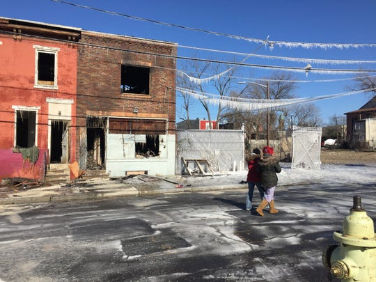 Two women walk past burned-out buildings on the 400 block of Chestnut Street in Camden Thursday.