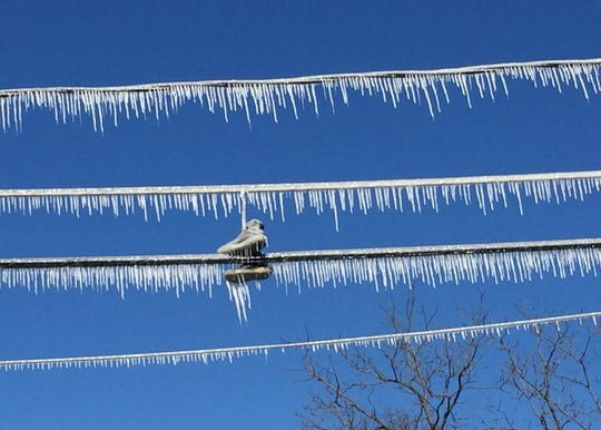 Frozen sneakers dangle on ice-covered wires Thursday at a fire scene on the 400 block of Chestnut Street in Camden.