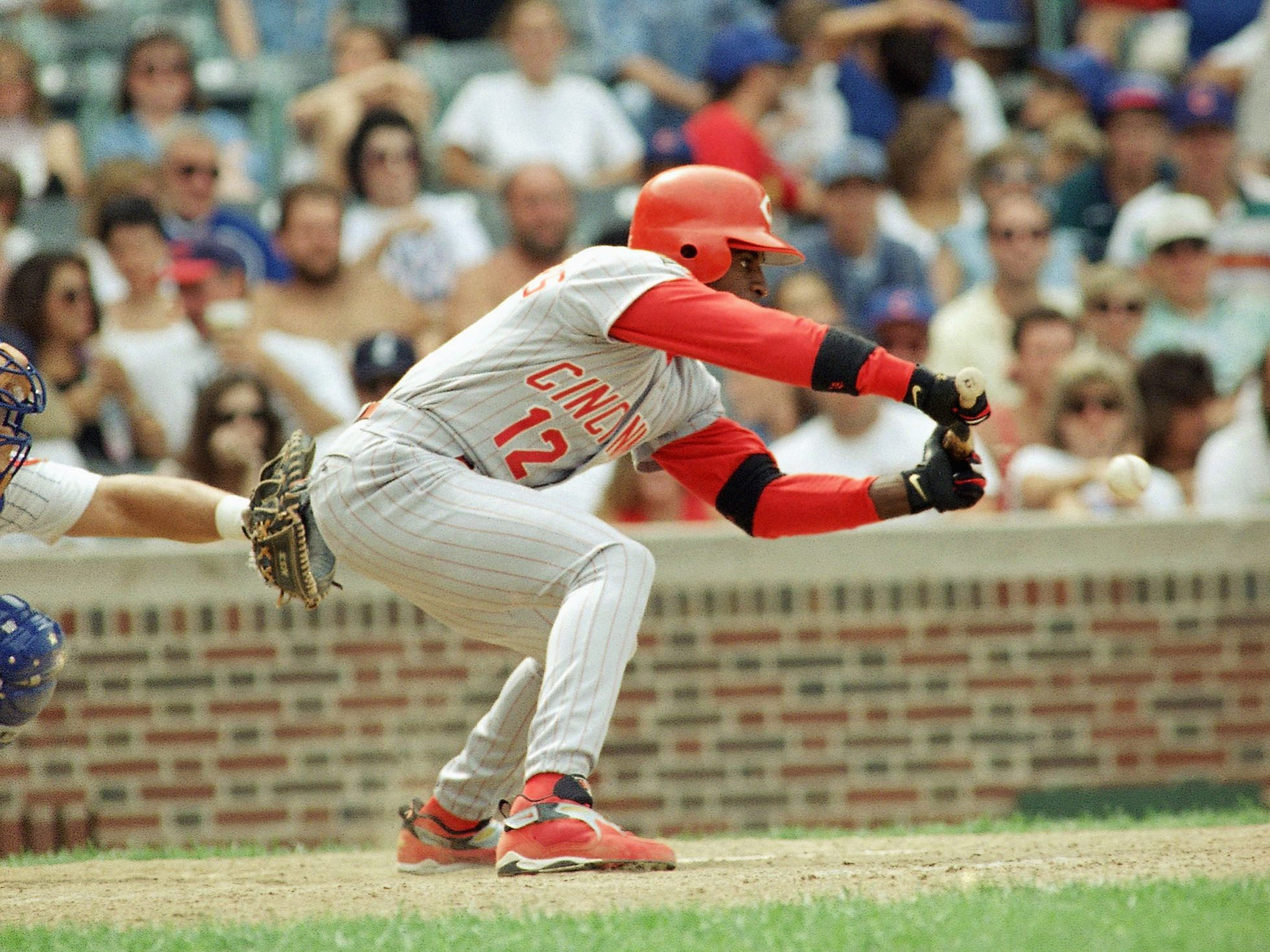 Cincinnati Reds' Deion Sanders bunts as Chicago Cubs catcher Mark Parent waits for the ball in the 8th inning on Sunday, July 24, 1994 in Chicago. The Cubs beat the Reds 3-0. (AP Photo/Doug Atkins)