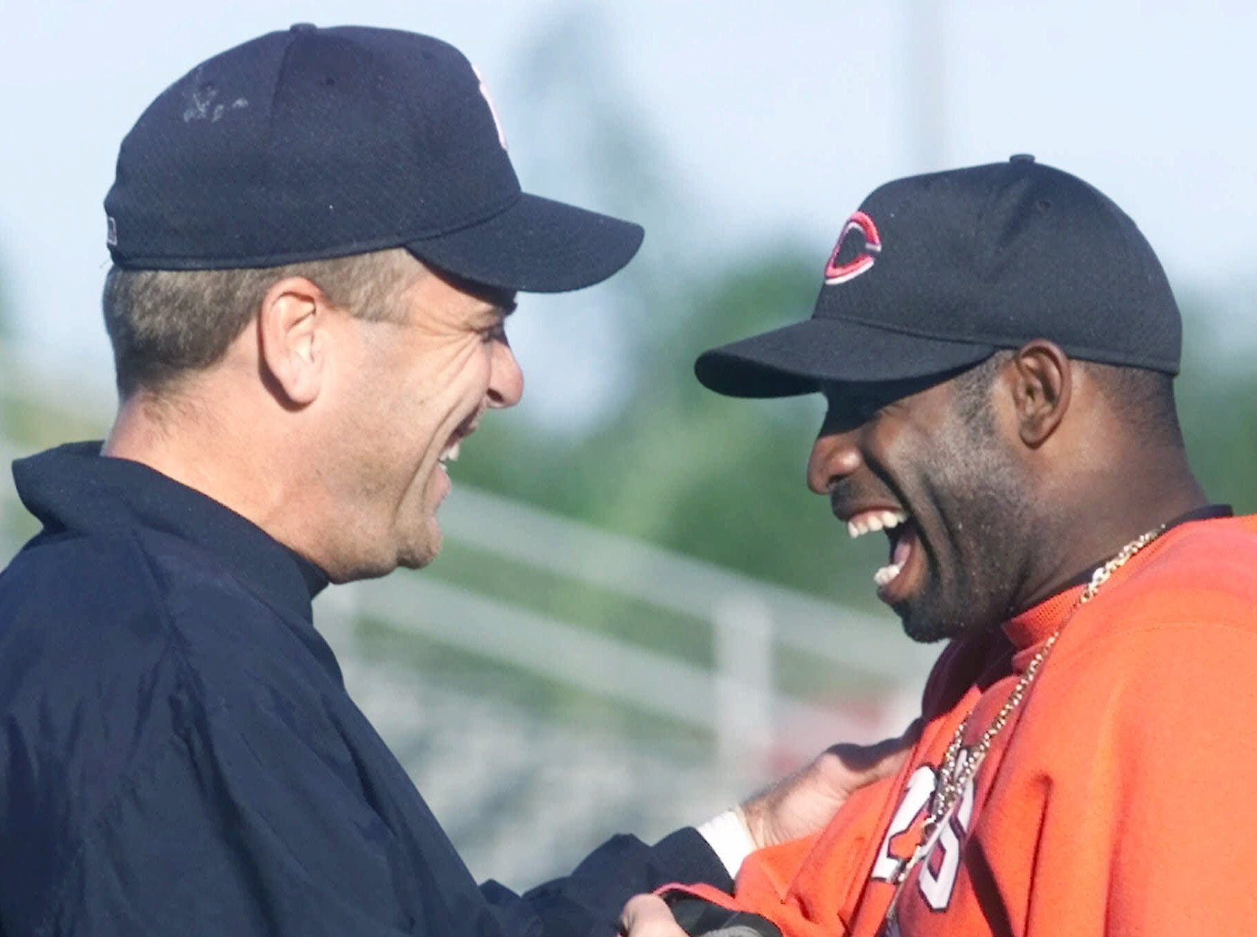Text: New York Yankees catcher Joe Oliver, left, and Cincinnati Reds outfielder Deion Sanders enjoy a laugh during batting practice prior to their exhibition game Tuesday, March 6, 2001, in Sarasota, Fla. Oliver and Sanders were teammates on the 1997 Reds. (AP Photo/Al Behrman)