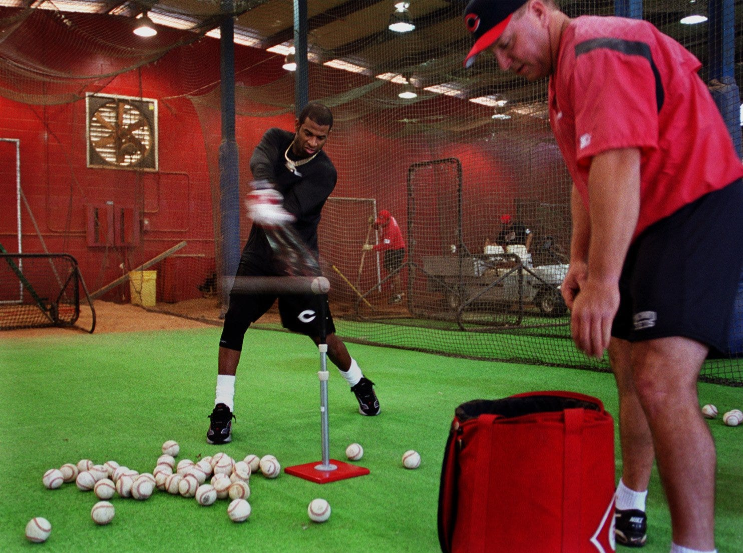 Text: 2000.0216.06.01 REDS Cincinnati Reds spring training invitee Deion Sanders takes a few swings off the batting tee as Reds coach Donnie Scott sets up the balls for him. Sanders is keeping lower profile while quietly working behind the scenes out of the view of the public. He is trying to get himself in baseball condition and working the kinks out of his bothersome knee. Cincinnati Enquirer/Michael E. Keating