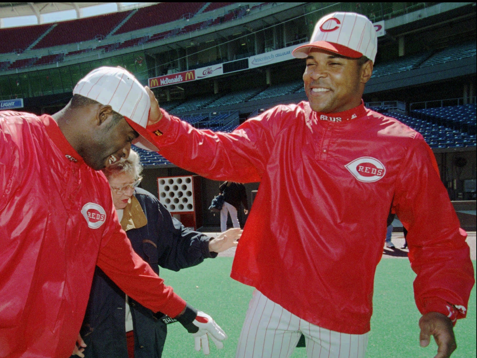 Text: Cincinnati Reds shortstop Barry Larkin, right, slaps Deion Sanders on the head as Sanders jokes with Larkin and Reds owner Marge Schott, center, during practice Monday, March 31, 1997, in Cincinnati. The Reds open against the Colorado Rockies Tuesday afternoon. (AP Photo/Al Behrman)