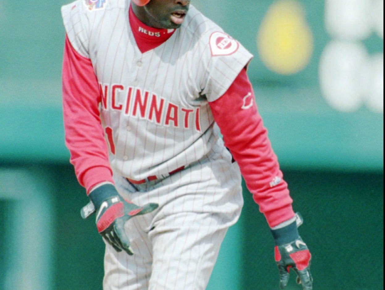 Text: Cincinnati Reds' Deion Sanders leads off after stealing second base in the first inning of the Reds' 13-4 loss to the Colorado Rockies at Denver's Coors Field Wednesday, April 9, 1997, in Denver. Sanders has modified his uniform by cutting off the sleeves of his shirt and wearing high-pantlegs, a move that he says is a tribute to baseball's first black player Jackie Robinson but which has raised questions of National League officials who are looking into his attire. (AP Photo/David Zalubowski)