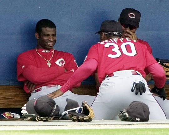 Text: Cincinnati Reds Deion Sanders, left, laughs at teammate Ken Griffey Jr. during a game against the Texas Rangers Monday, March 27, 2000, in Port Charlotte, Fla. (AP Photo/Pat Sullivan)
