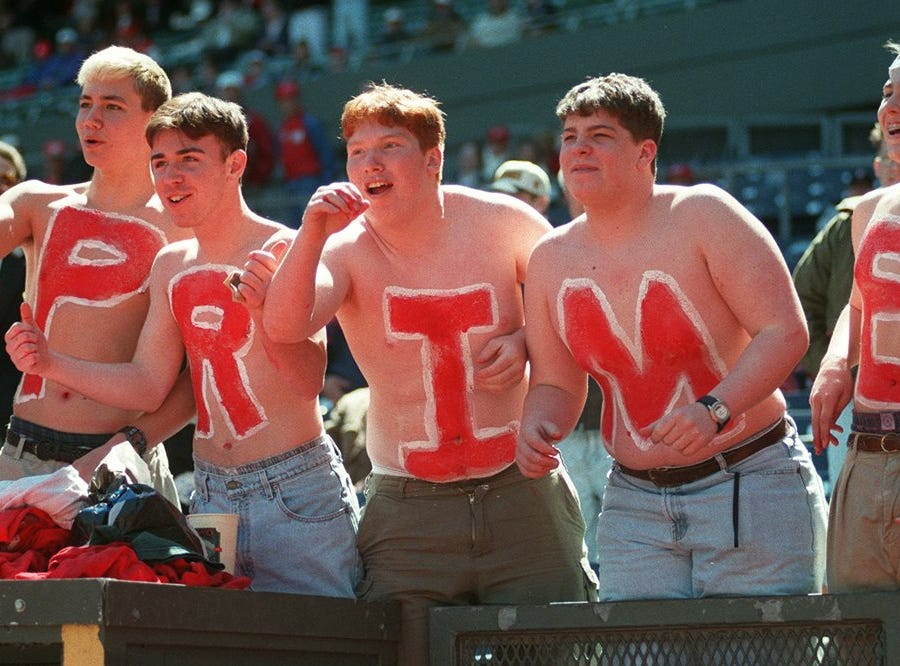 Text: reds prime metro 4/1/97 these bare-chested deion sanders fans from centerville, ohio are left to right chad stull, rob wilder, ryan oeters, rob ellinger and zach parks. on their backs is time! cincinnati enquirer/michael e. keating mek