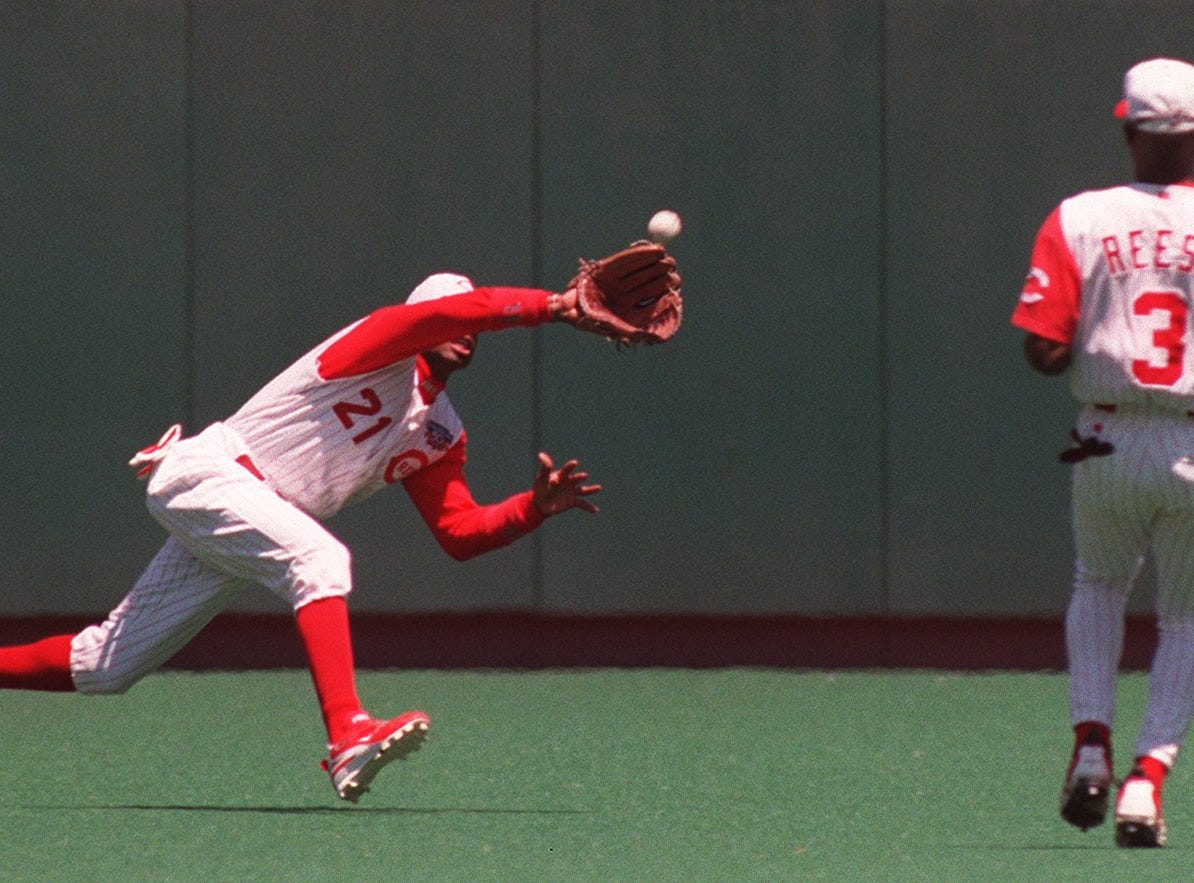 Text: 1997.0615.08.1-REDS-Deion Sanders makes a first inning diving catch in center field as Pokey Reese, right, looks on during Sunday's game against the White Sox. Chris Snopek was out on the play. Photo by Kevin J. Miyazaki/Cincinnati Enquirer.km