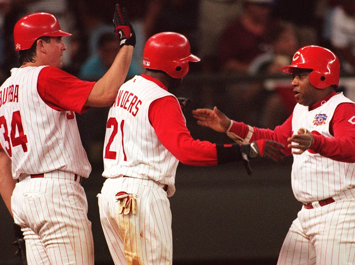Text: 1997.0701.10.2 REDS WIN --Reds Terry Pendleton is greeted at the plate by Deion Sanders and Dave Burba after he knocked them in on a grand slam in the seventh inning. Pendleton also sent Curtis Goodwin home. The Reds defeated Milwaukee for the second day in a row. Photo by Craig Ruttle/Cincinnati Enquirer