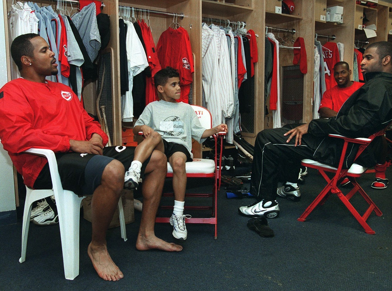 Text: 2000.0328.06.01 Reds capt. Barry Larkin, with son Shane -7- at his side, sits in conversation with Deion Sanders and Alex Ochoa in the reds Sarasota clubhouse. For use with story about Larkin and his senior status. Cincinnati Enquirer/Michael E. Keating mek