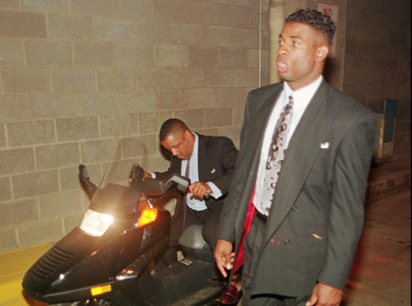 """Text: Cincinnati Reds outfielder Deion Sanders walks along behind the jury, while Sports Marketing agent Wayne """"Box"""" Miller parks the scooter Sanders was riding Aug. 8, 1994, as they tour the scene of the motor scooter incident at Riverfront Stadium in Cincinnati Monday, May 22, 1995. The charges, all misdemeanors, stem from an alleged incident on Aug. 8 involving an off-duty Cincinnati police officer working in uniform as a security guard at Riverfront Stadium. The charges include resisting arrest, driving without a license, failure to comply and leaving the scene of an accident. (AP Photo/Tom Uhlman)"""