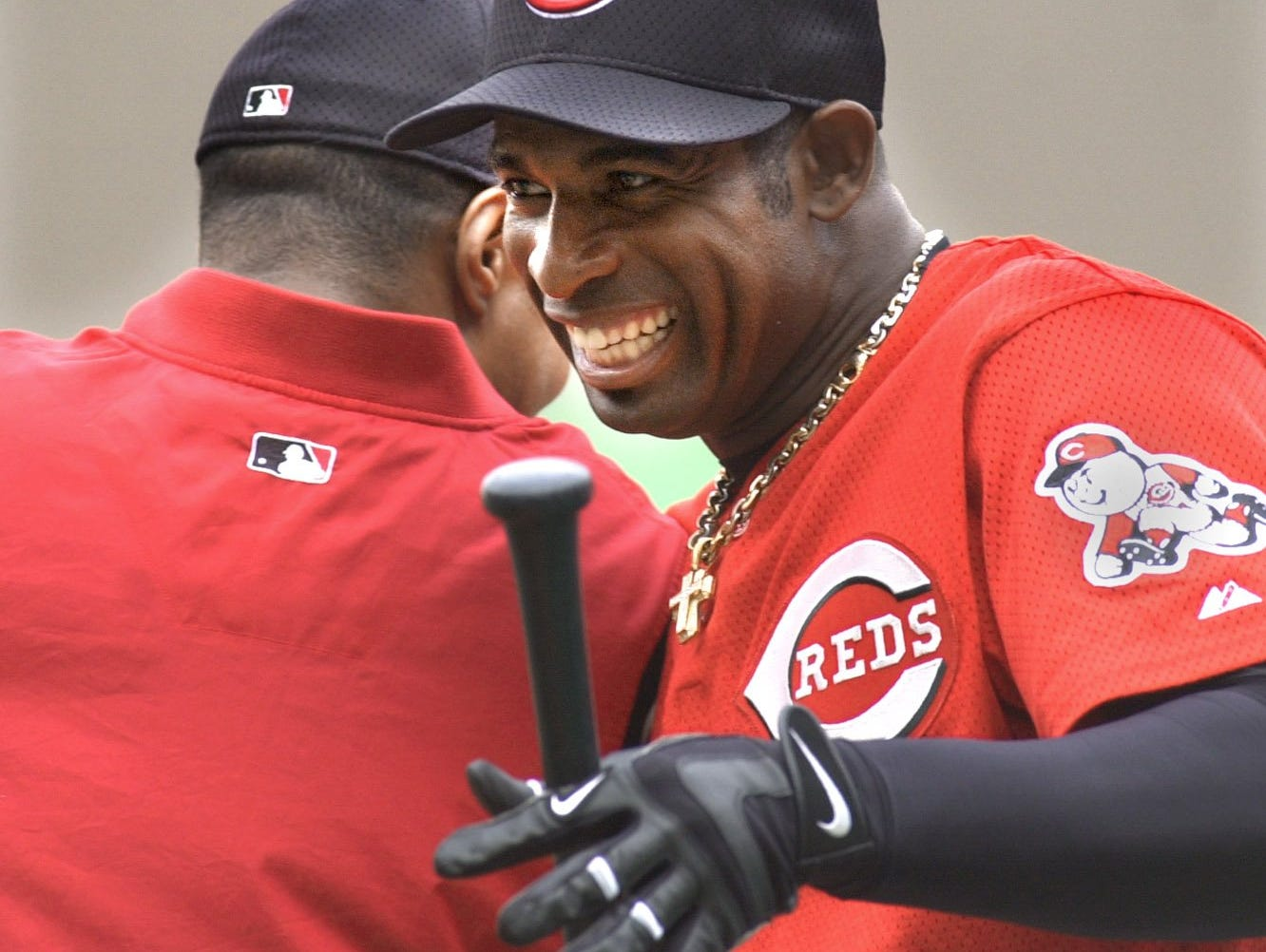 Text: 2001.0501.10.1--DEION RETURNS--Deion Sanders goofs around with Barry Larkin at Cinergy Field Tuesday May 2, in the afternoon during batting practice. Sanders returned to the Reds and the majors after several seasons and other careers. Photo by Craig Ruttle/Cincinnati Enquirer