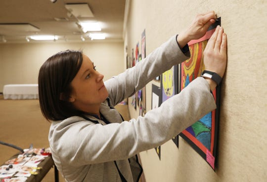 Jennifer Bush director of the Johnson-Humrickhouse Museum in Coshocton, hangs a piece for the Playground of Color show on Thursday. The exhibition features works from elementary school students from around the county.