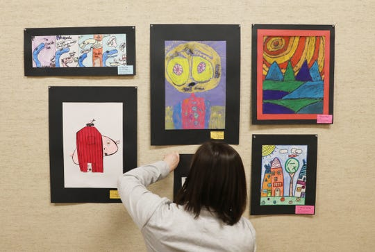 Jennifer Bush hangs pieces for the Playground of Color exhibition at the Johnson-Humrickhouse Museum.