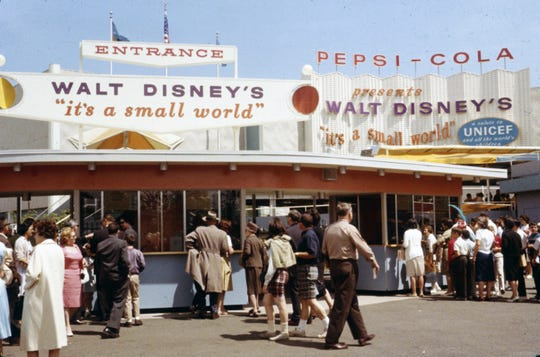 """This 1964 file photo provided by Disney, shows visitors to the """"It's a Small World"""" attraction at the 1964 World's Fair in New York. Racine artist Joyce Carlson worked on the model for both the ride and several of the singing dolls."""