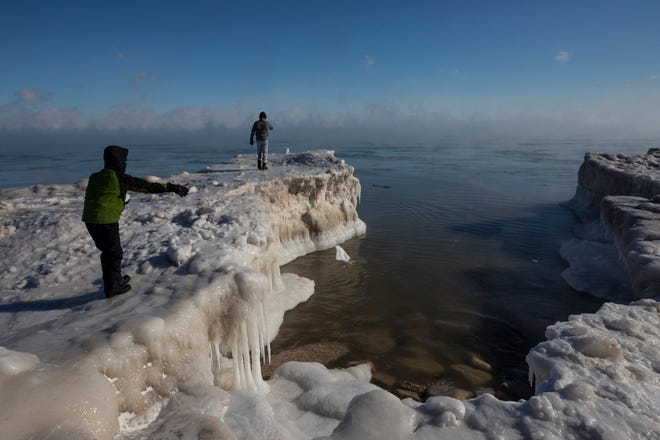 A young boy tosses a chunck of snow into Lake Michigan Wednesday, Jan. 30, 2019 in Milwaukee.