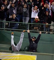 Red Sox fans and Boston police officer Steve Horgan celebrate as Tigers outfielder Torii Hunter falls over the right-field fence into the bullpen trying to catch a grand slam hit by Boston Red Sox' David Ortiz during Game 2 of the 2013 American League Championship Series.