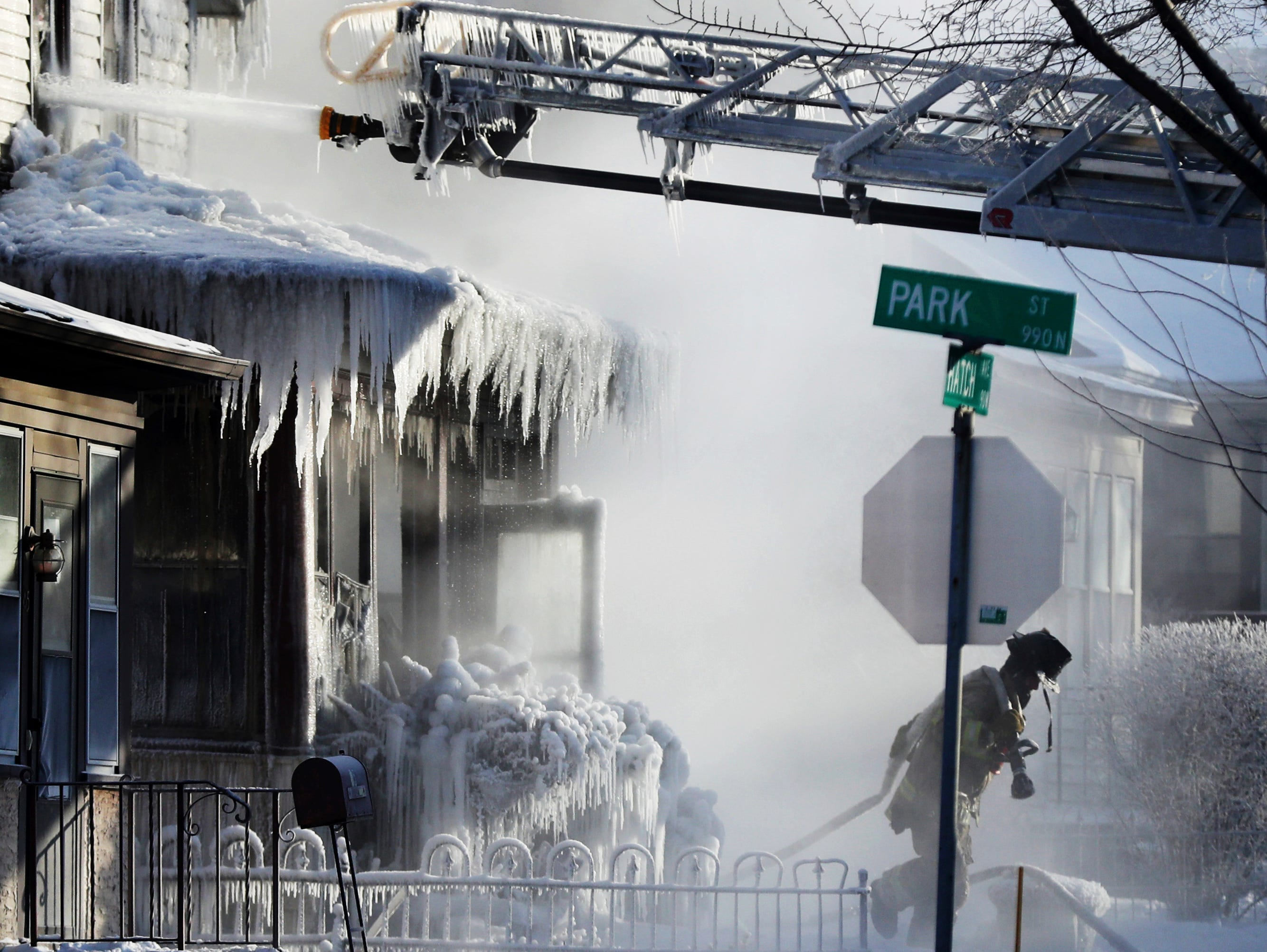 St. Paul firefighters at the scene of a house fire during an arctic deep freeze on Wednesday, Jan. 30, 2019, In St. Paul, Minn.