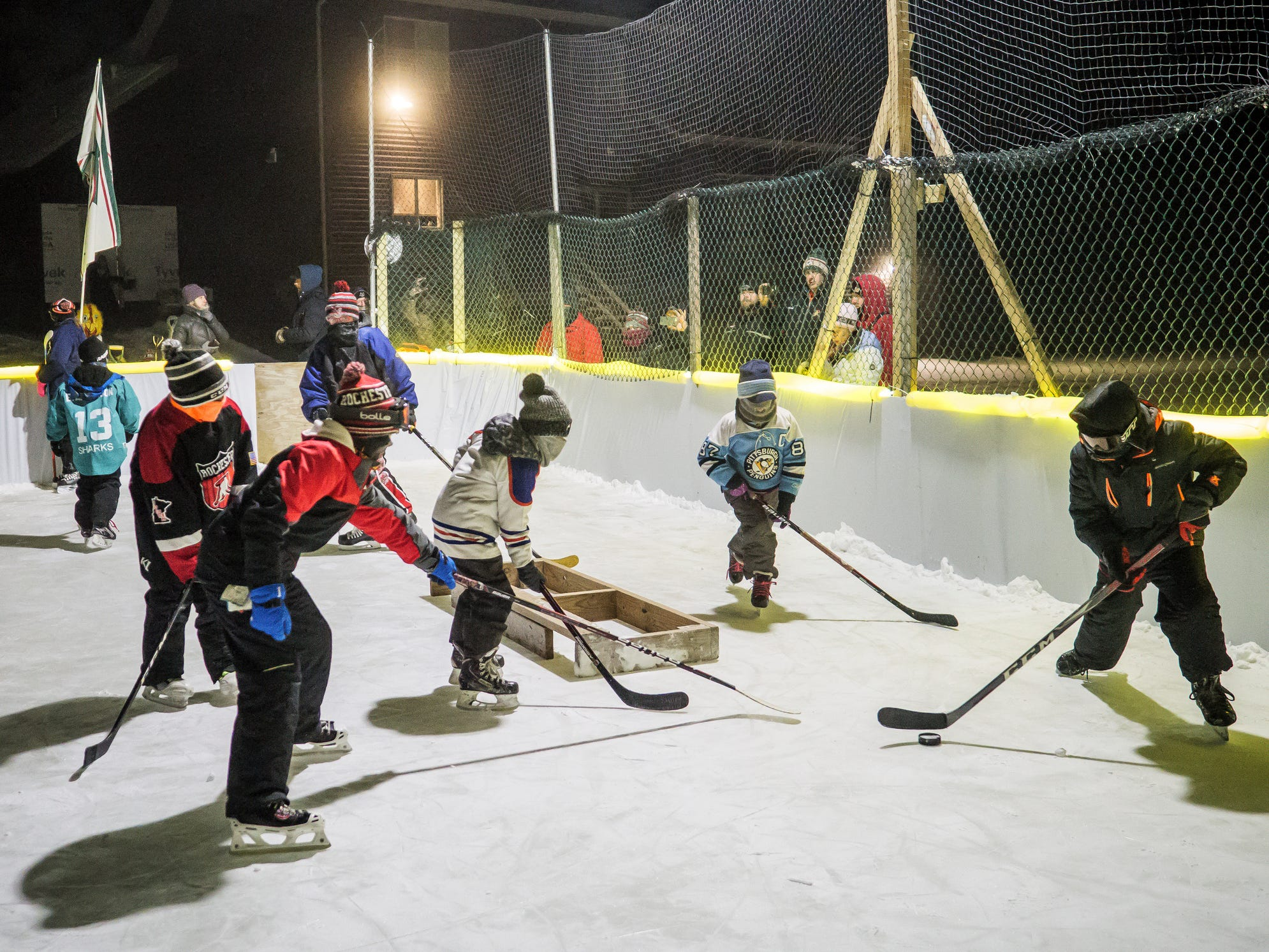 Hockey players chase the puck during an attempt at the Guinness Book of World Records record for coldest hockey game played Thursday,  Jan. 31, 2019, in the backyard belonging to Mike Burman in northwest Rochester, Minn. About 25 kids took to the ice in the attempt. The air temperature, according to the National Weather Service, was in the high negative 20s, and the wind chill was in the mid-negative 40s.
