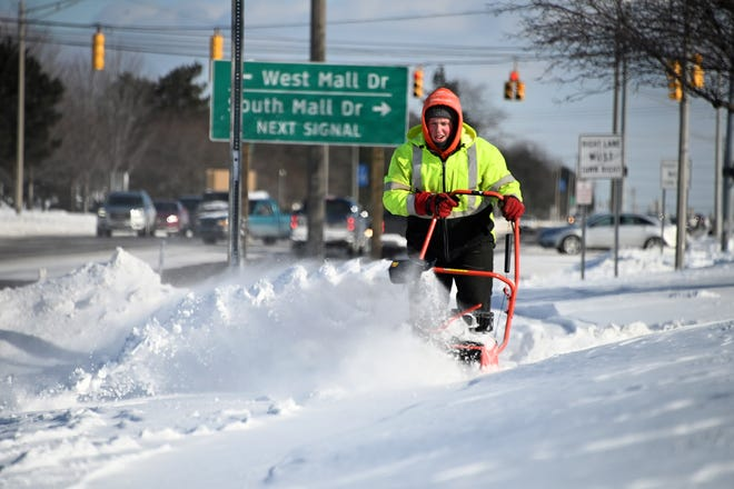 Kyle Stewart plows through drifted snow while trying to clear a sidewalk outside a Lansing-area shopping mall on Thursday, January 31, 2019. The walks had been cleared recently, but blowing and drifting quickly closed them again.