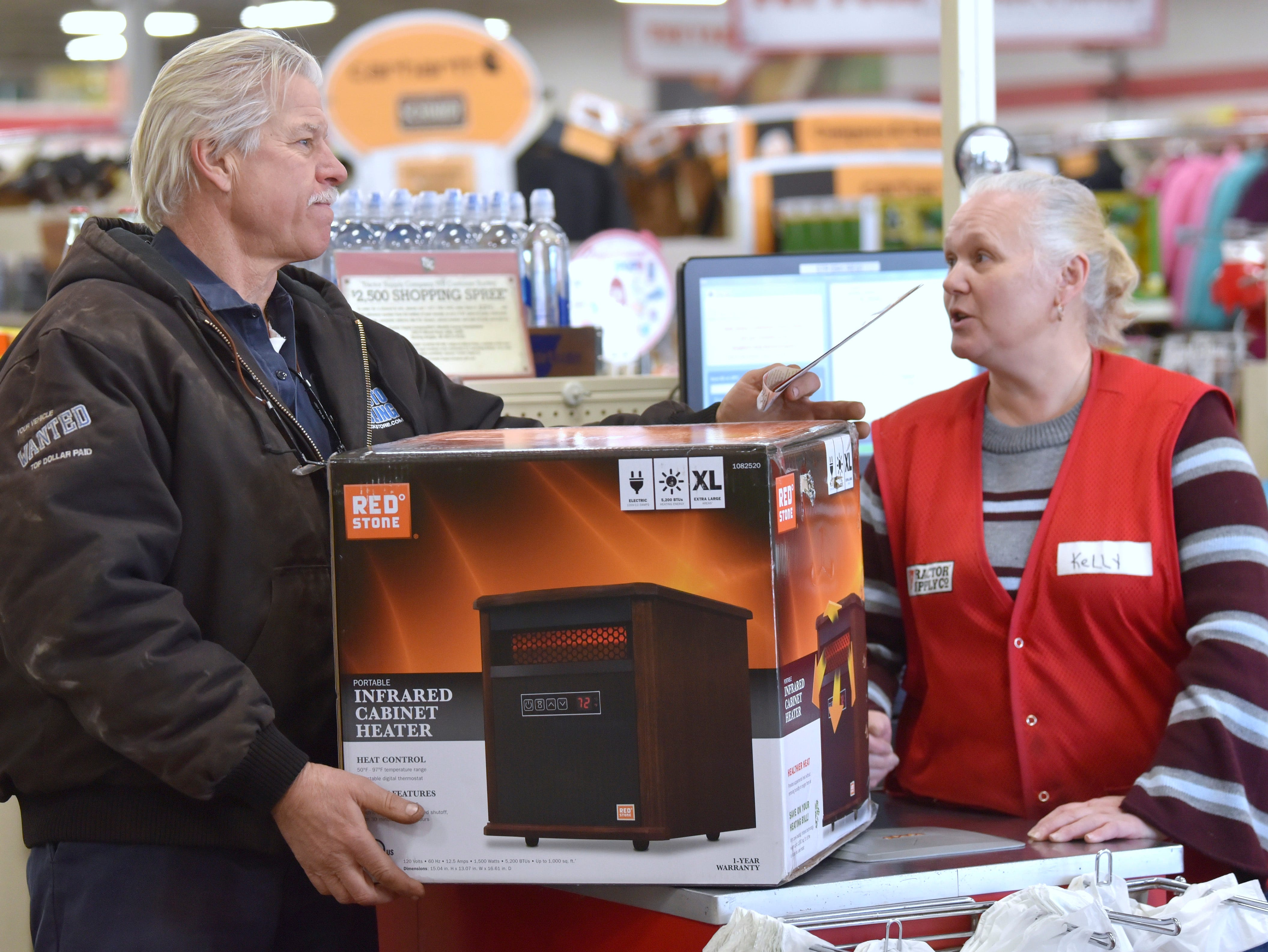 Lenox Township's Kustom Truck and Trailer owner Michael Kotulski, of Algonac, buys an XL infrared electric heater from New Haven's Tractor Supply Co. cashier Kelly Haggard, of Marine City, Thursday morning, January 31, 2019. One of Kotulski's hot-water boiler pumps broke at home, so he needs to heat the area while the unit gets repaired.