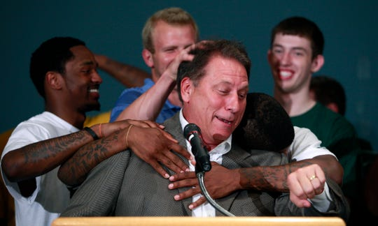In this 2010 file photo, Michigan State basketball coach Tom Izzo, center, is hugged by players, including Kalin Lucas, left, Austin Thornton, center rear, Korie Lucious, right front, and Garrick Sherman, right rear, during a news conference in East Lansing announcing that he will stay at Michigan State instead of moving to the NBA  to coach the Cleveland Cavaliers.