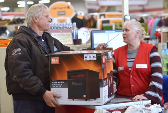 Lenox Township's Kustom Truck and Trailer owner Michael Kotulski, of Algonac, buys an XL infrared electric heater from New Haven's Tractor Supply Co. cashier Kelly Haggard, of Marine City.
