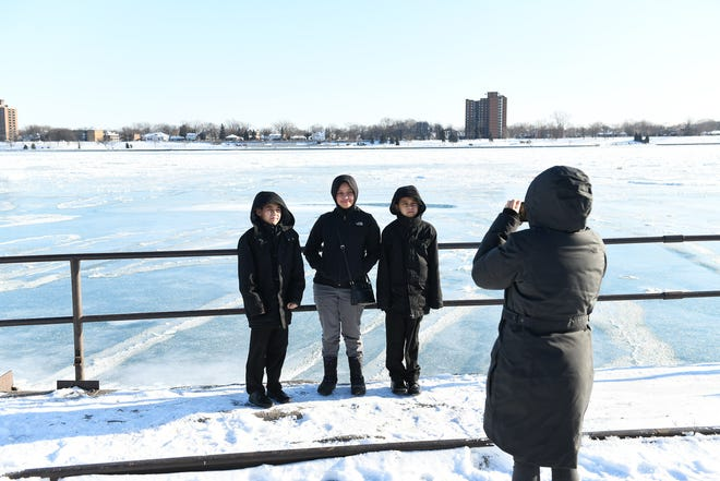 Gloria Santillan of Detroit takes photos of her children in front of the mostly frozen Detroit River in Detroit on Jan. 30, 2019.  They are, from left, Mattius Santillan, 10, Arabelle Santillan, 13, and Joaquin Santillan, 8. Santillan.