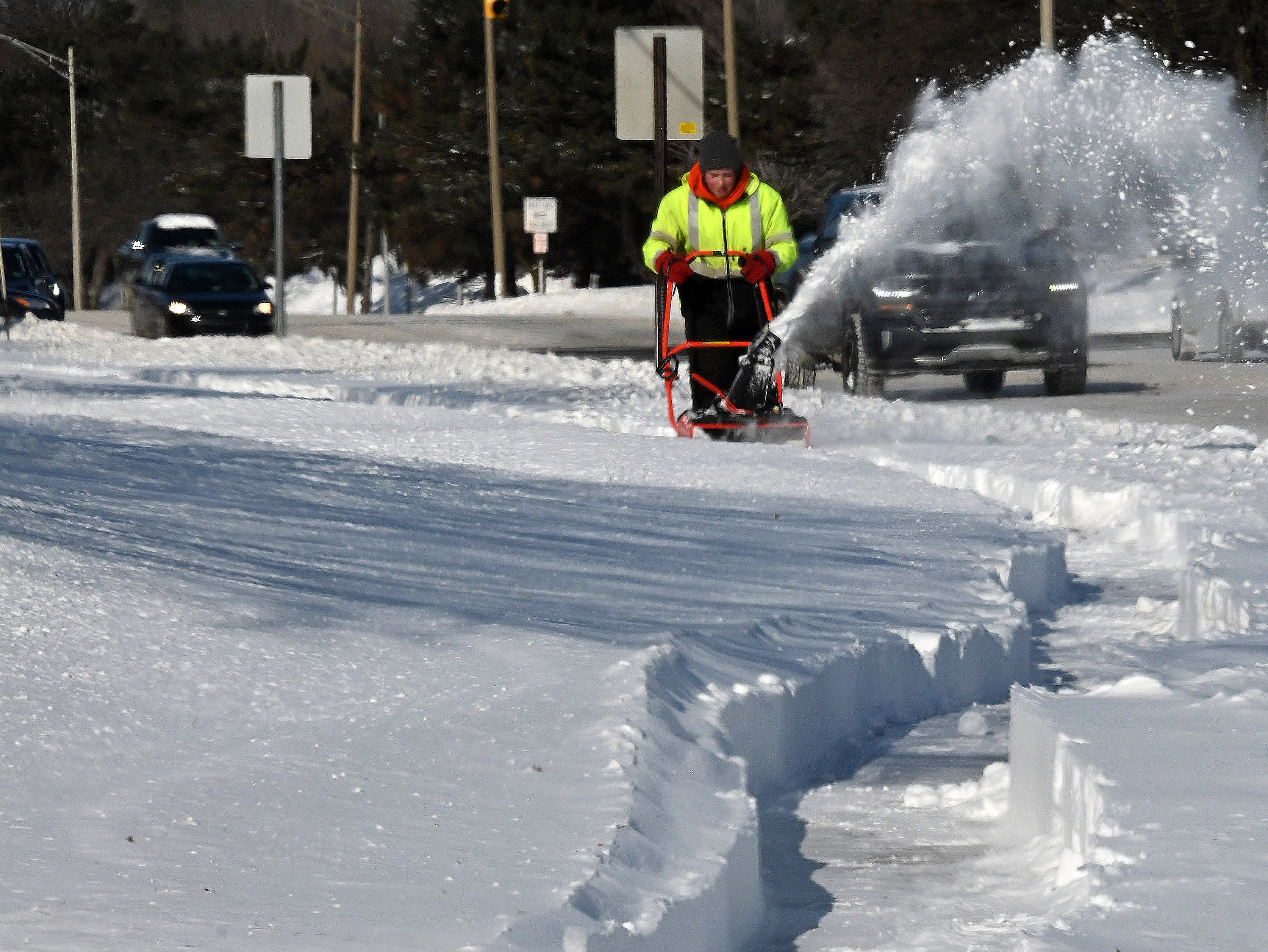 Kyle Stewart plows through drifted snow while trying to clear a sidewalk outside a Lansing-area shopping mall  Thursday.