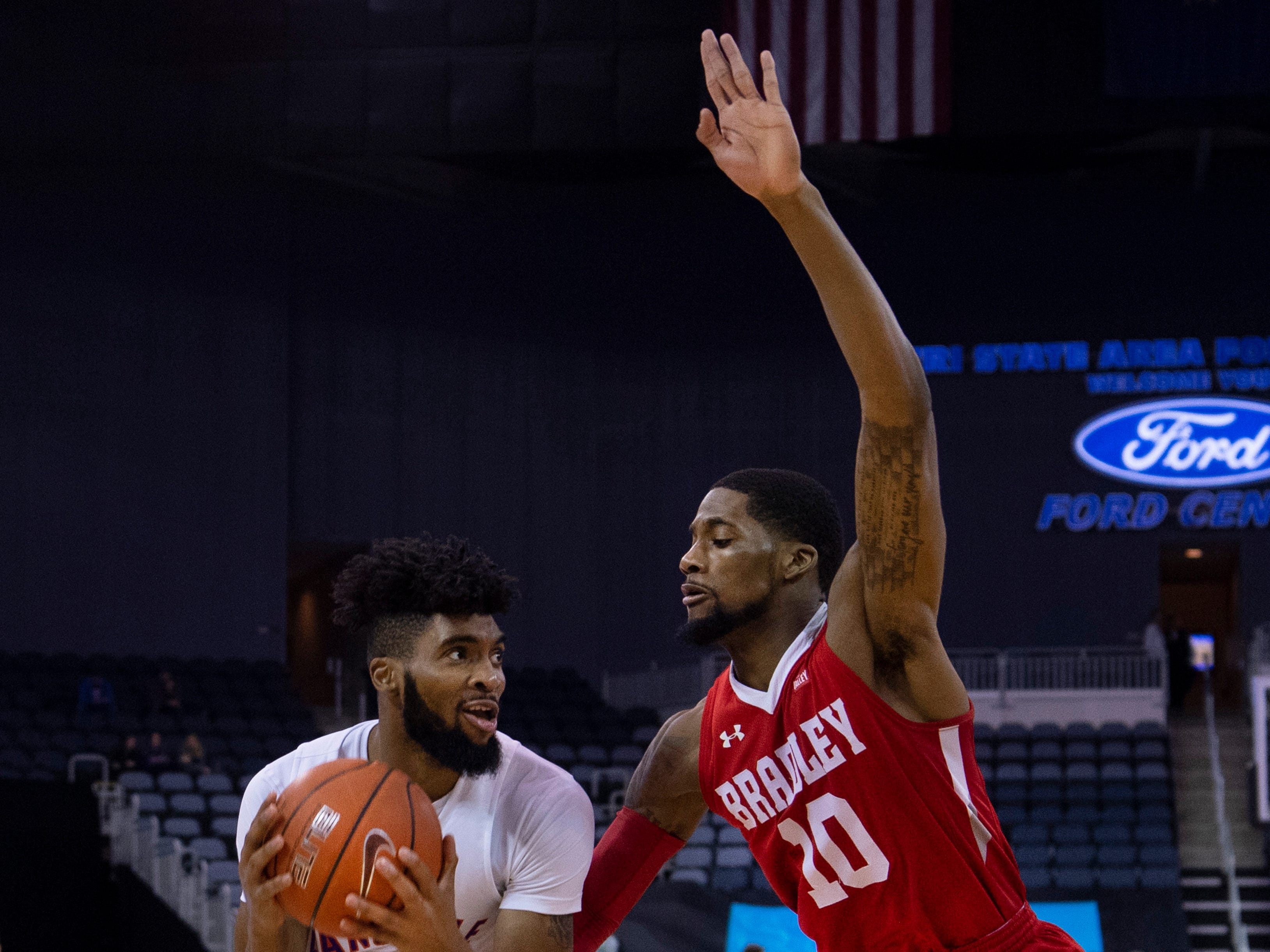 Evansville's K.J. Riley (33) drives past Bradley's Elijah Childs (10) for a basket and the foul during their game at the Ford Center Wednesday night.
