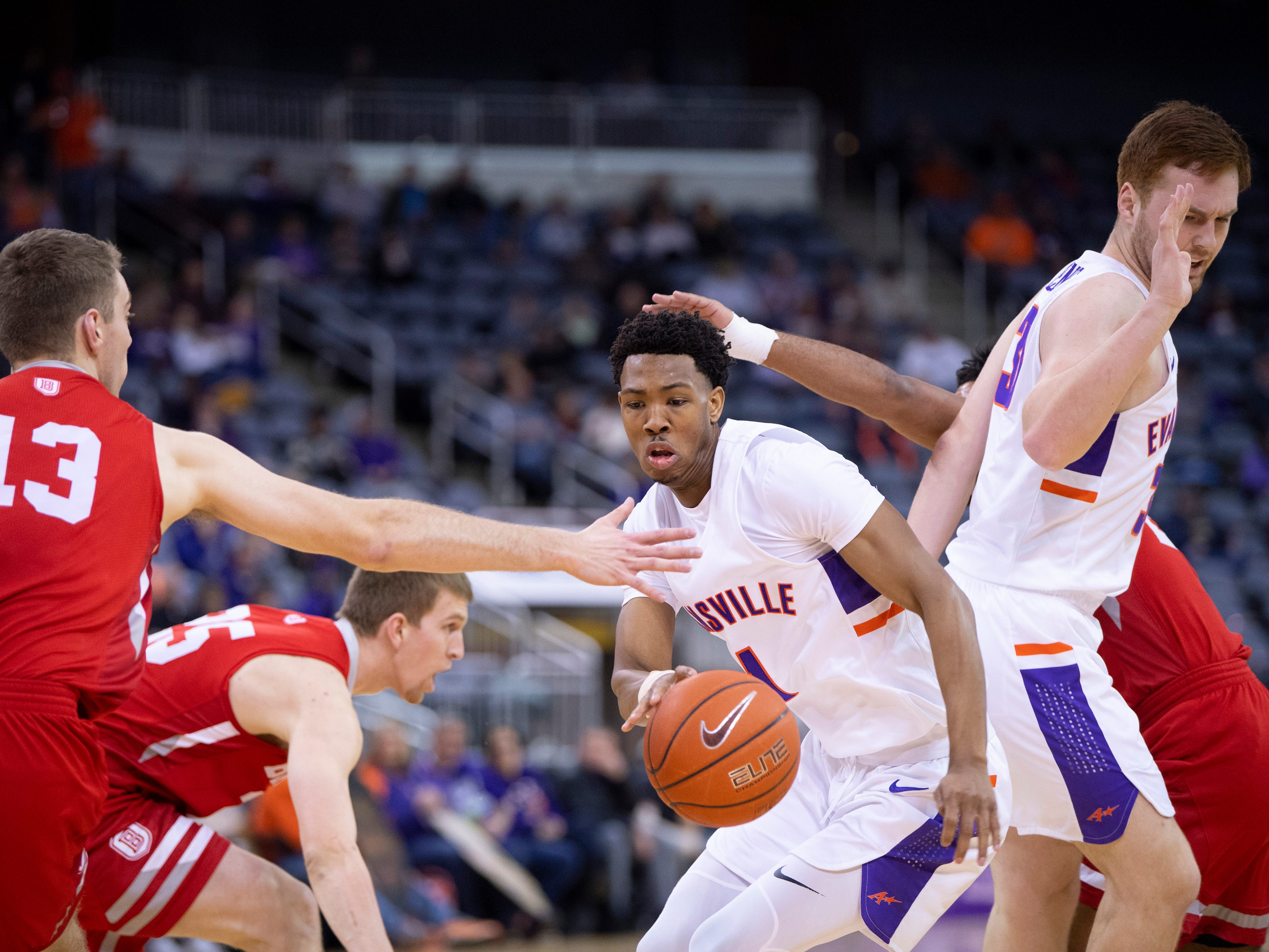 Evansville's Marty Hill (1) maneuvers through the defense of Bradley's Nate Kennell (25) and Luuk van Bree (13) during their game at the Ford Center Wednesday night.