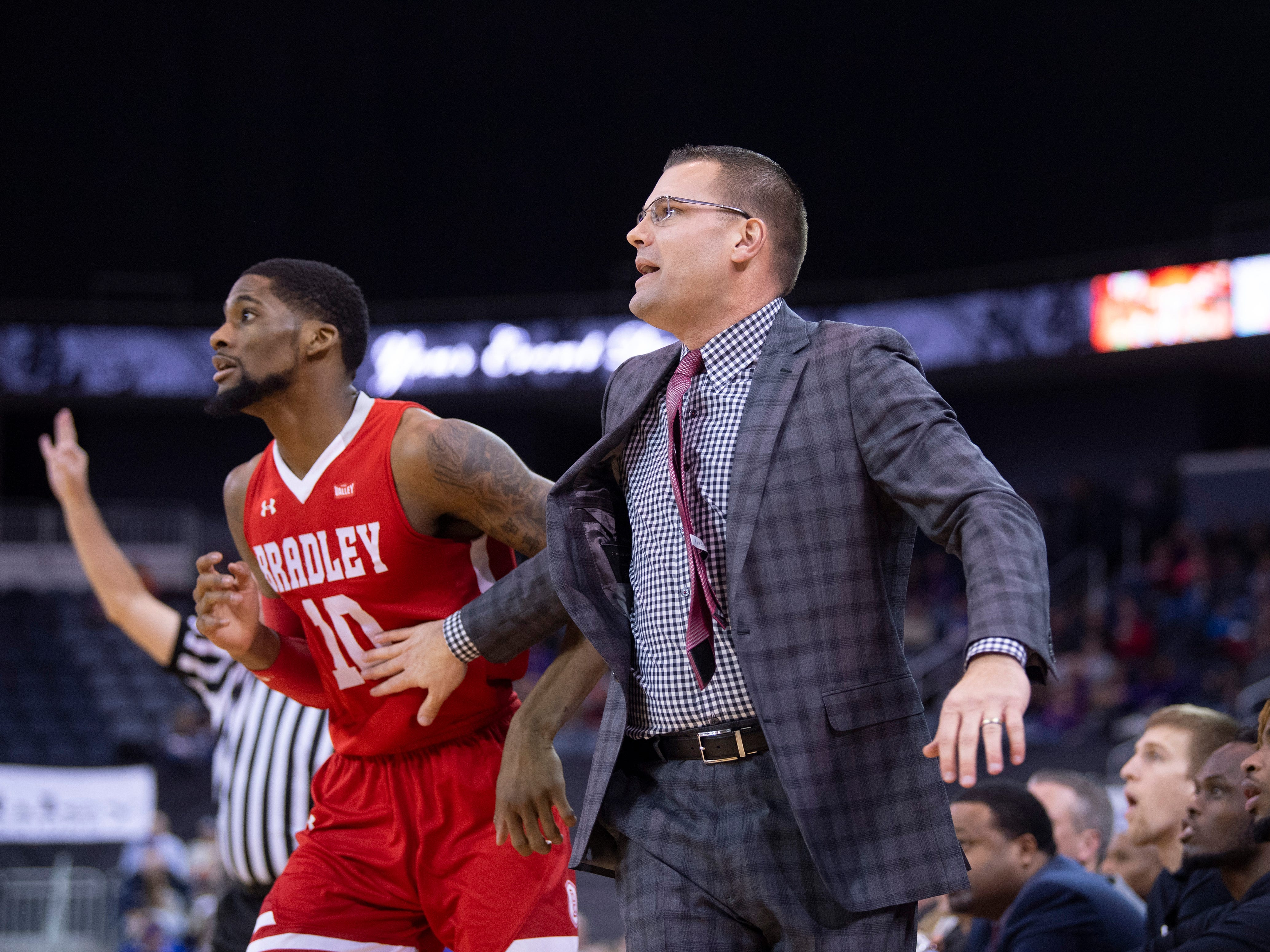 Bradley University Head Coach Brian Wardle holds Bradley's Elijah Childs (10) back as Evansville put up a 3-pointer during their game at the Ford Center Wednesday night.