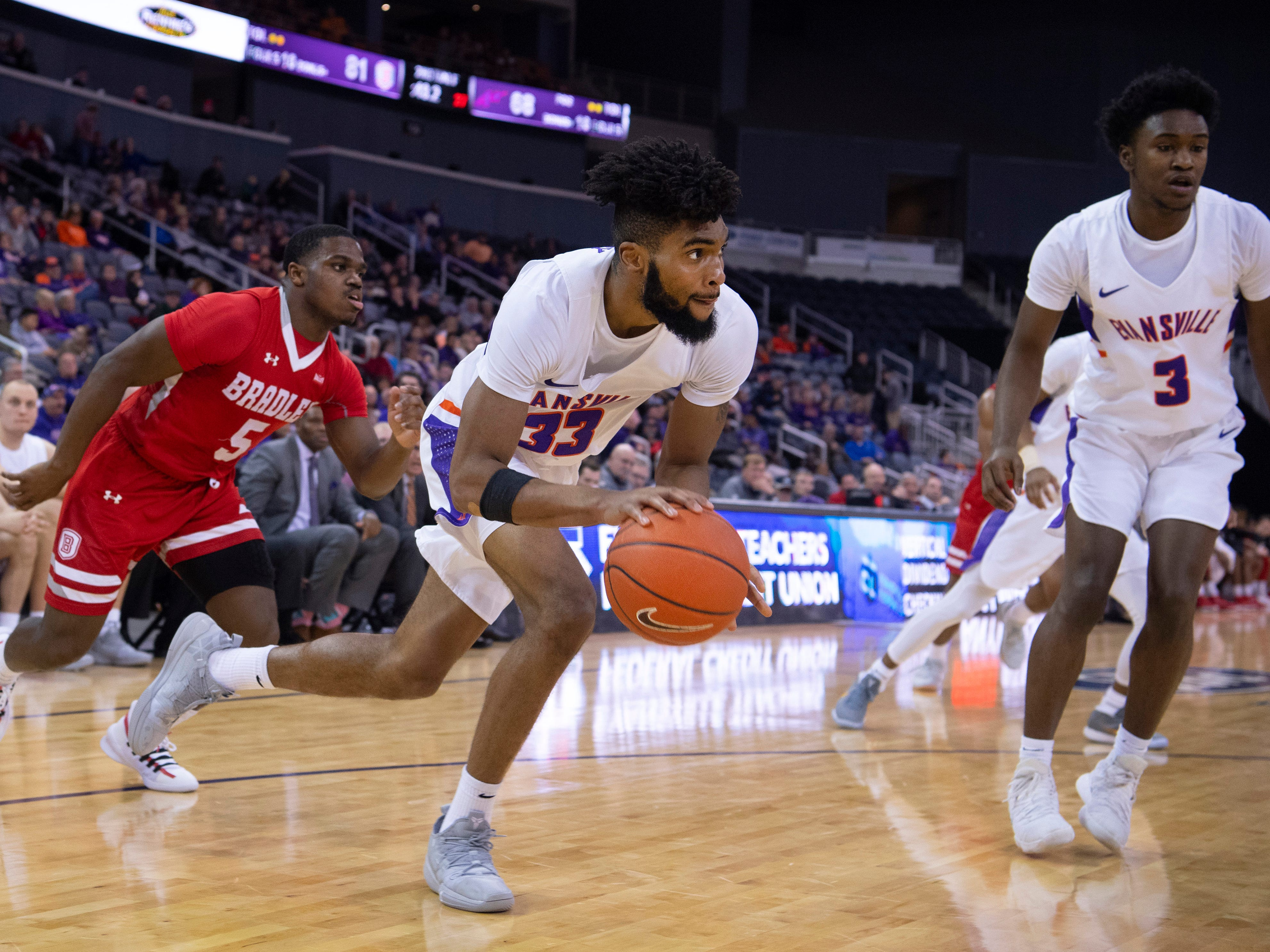 Evansville's K.J. Riley (33) drives to the basket for two points after making a steal against Bradley during their game at the Ford Center Wednesday night.