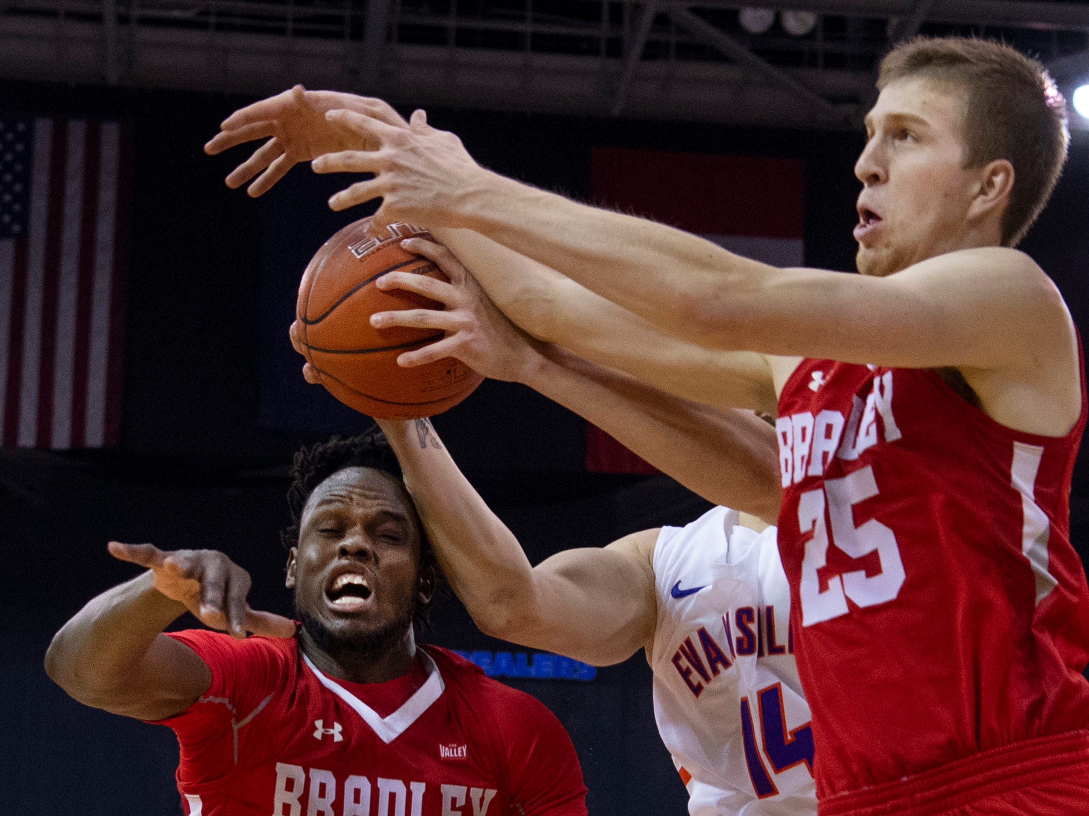 Bradley's Koch Bar (12) takes a forearm from Evansville's Dainius Chatkevicius (14) to the head as Bradley's Nate Kennell (25) defends during their game at the Ford Center Wednesday night.