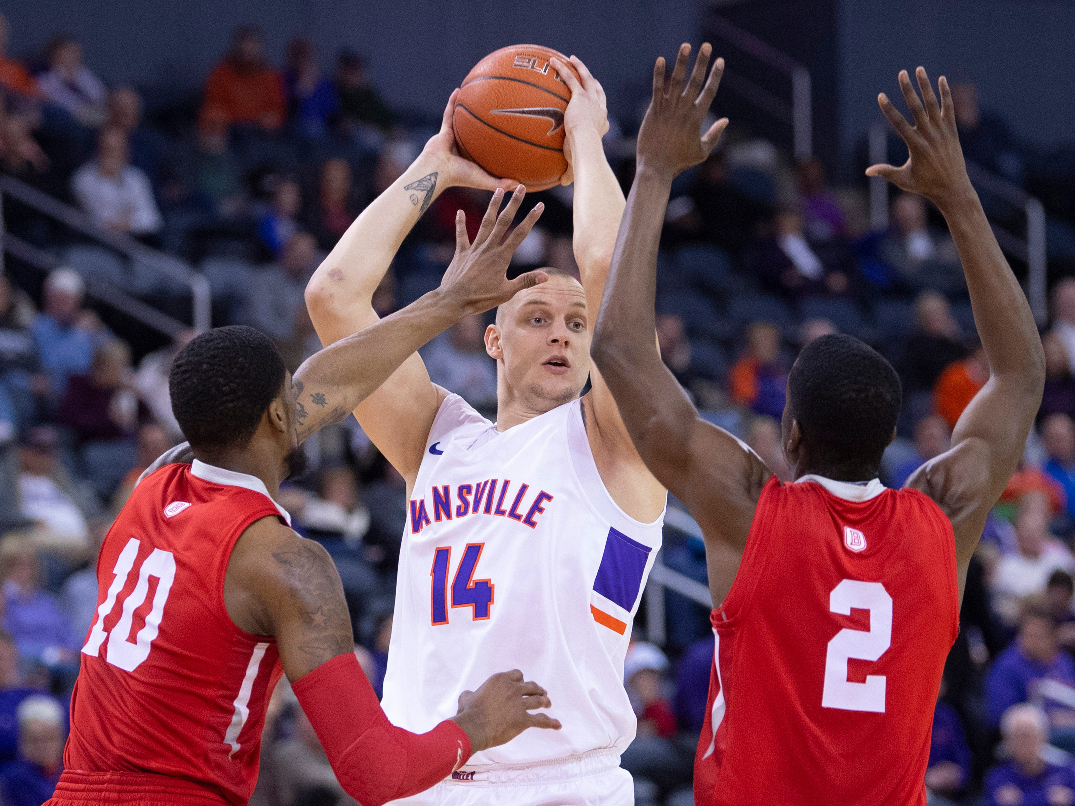 Evansville's Dainius Chatkevicius (14) looks to pass while being guarded by Bradley's Elijah Childs (10) and Luqma  Lundy (2) during their game at the Ford Center Wednesday night.