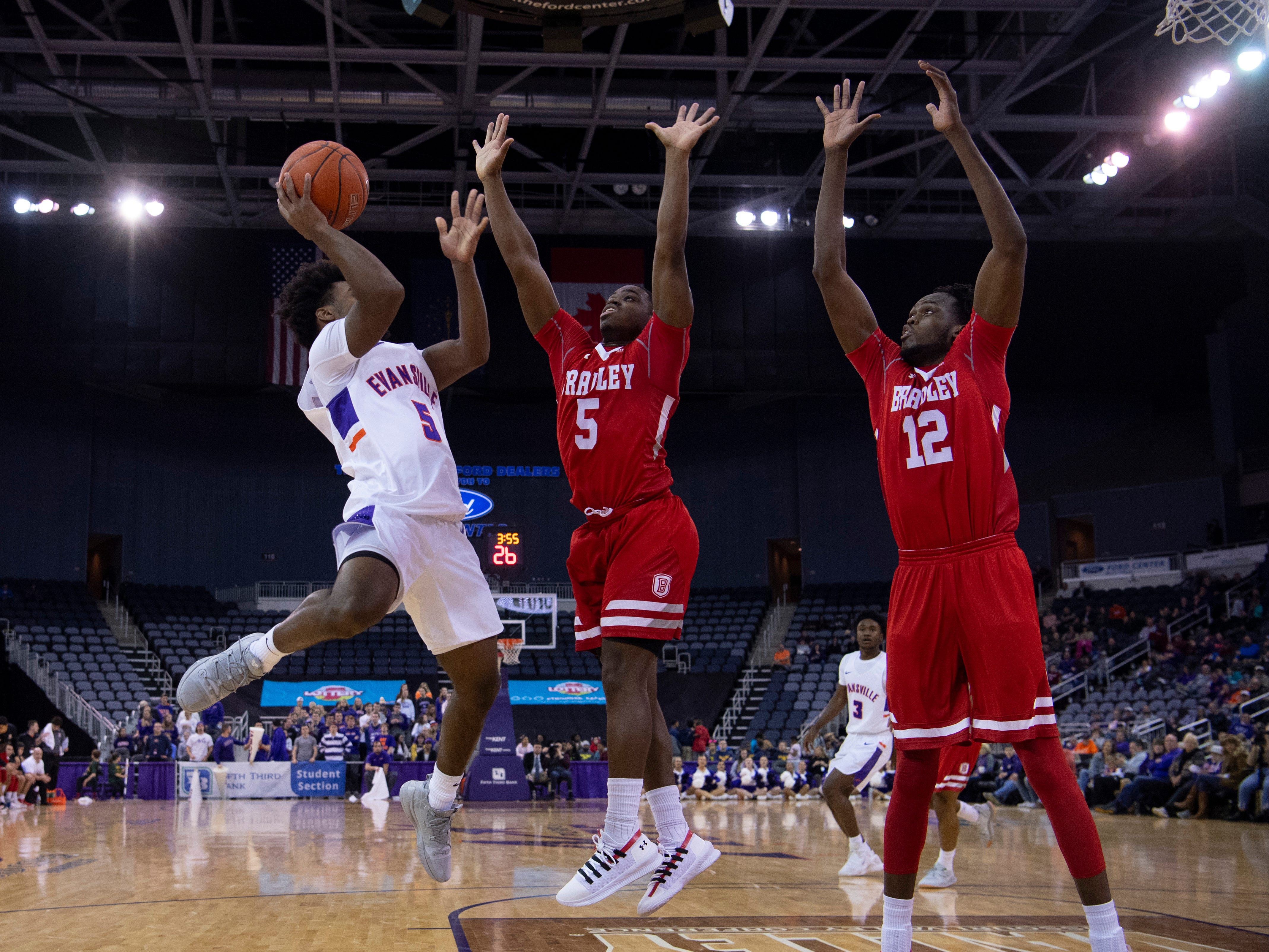 Evansville's Shamar Givance (5)  pulls up for a shot over Bradley's Darrell Brown (5) and Koch Bar (12) during their game at the Ford Center Wednesday night.