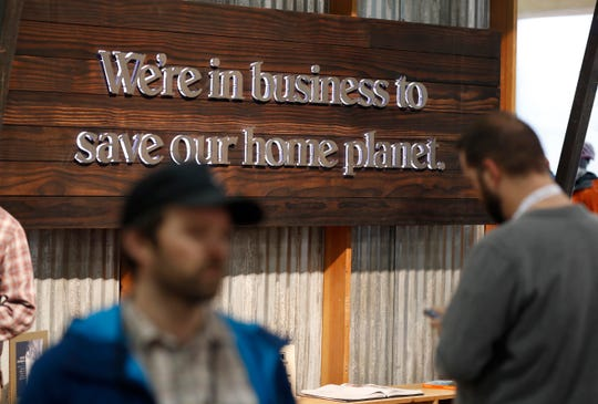 In this Wednesday, Jan. 30, 2019, photograph, buyers pass by a sign in the Patagonia exhibit at the Outdoor Retailer & Snow Show in the Colorado Convention Center in Denver. Major players in the outdoor industry jumped into the political fight over national monuments two years ago and now have added climate change and sustainable manufacturing to their portfolio. (AP Photo/David Zalubowski)