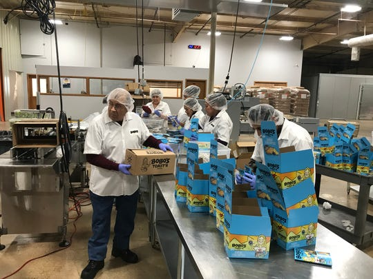 Factory workers package Bobo's snack products at the company's new Loveland factory.