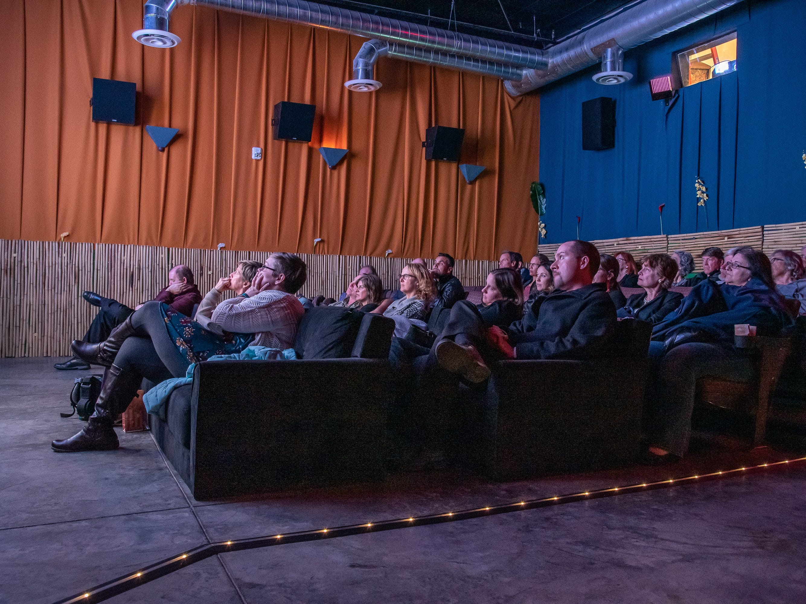 Attendees in an overflow room watch Fort Collins mayor Wade Troxell and City Manager Darin Atteberry on a large screen as they address a crowd during the annual State of the City Address on Tuesday, January 29, 2019, at the Lyric Cinema in Fort Collins, Colo.