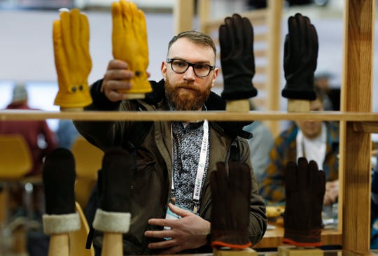 Theo Kerbourch of Ville St. Laurent, Quebec, Canada, looks over gloves for sale in the Hestia exhibit at the Outdoor Retailer & Snow Show Wednesday, Jan. 30, 2019, in the Colorado Convention Center in Denver. Major players in the outdoor industry have joined more than 900 other exhibitors to show their wares to the more than 25,000 attendees expected for the weekend event. (AP Photo/David Zalubowski)
