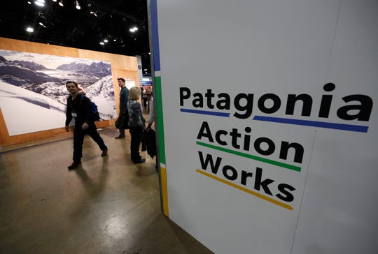 In this Wednesday, Jan. 30, 2019, photograph, a sign stands at the entrance to the Patagonia exhibit at the Outdoor Retailer & Snow Show in the Colorado convention Center in Denver. Major players in the outdoor industry jumped into the political fight over national monuments two years ago and now have added climate change and sustainable manufacturing to their portfolio. (AP Photo/David Zalubowski)