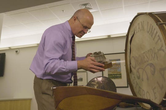 Tom Cimarusti, an associate professor of music, examines an instrument from the Koreshan Unity collection at Florida Gulf Coast University. The Koreshans were a religious sect that settled in Estero in the 1890s.